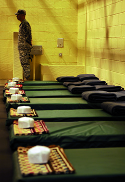Waiting for some dudes in orange jump suits: A US soldier stands guard next to beds with folded prayer mats and headwear in a common cell during a media tour of Bagram prison in November